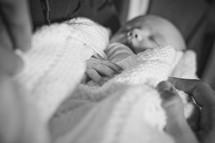 hands on swaddled sleeping newborn