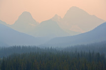 Forest fire smoke surrounding a mountain