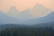 Forest fire smoke surrounding a mountain