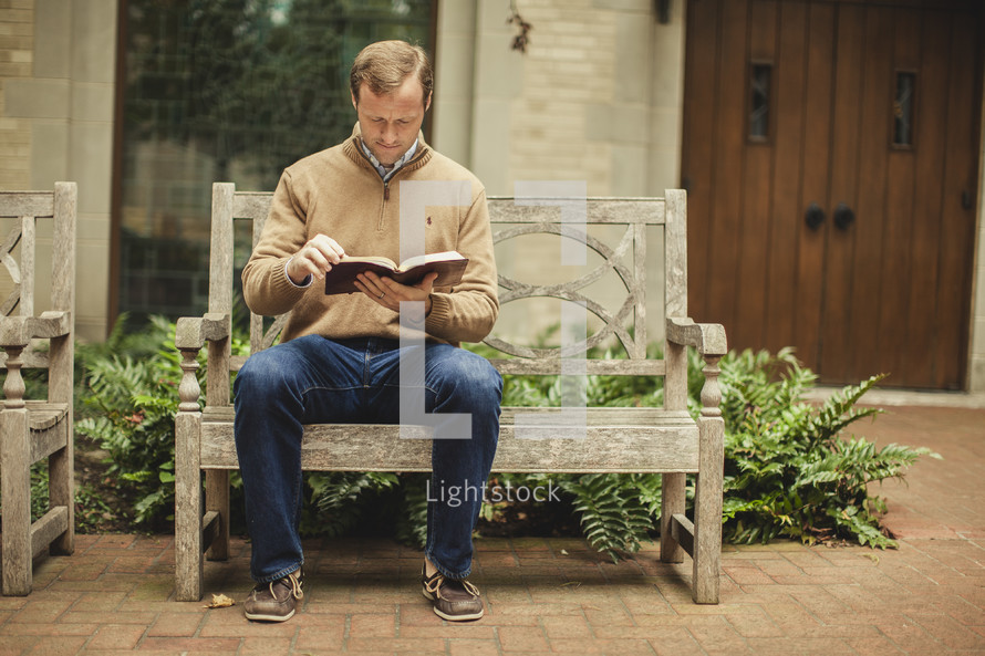 Man on bench reading Bible