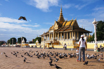 Mother and daughter feeding birds outside the Royal Palace in Cambodia