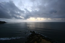 cloudy sky over the ocean and a rock jetty
