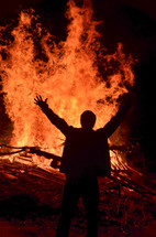 man standing with his hands raised in front of a bonfire