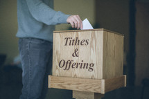 Man putting offering in wooden box.