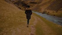 a woman walking beside a waterfall