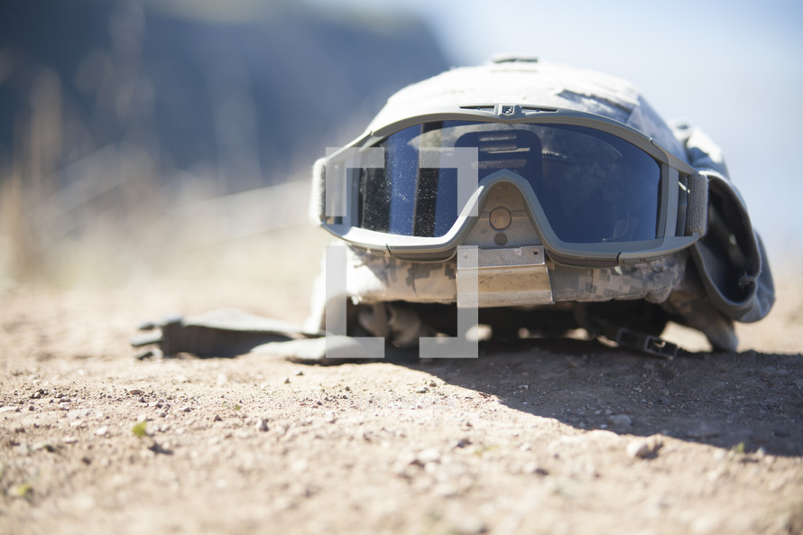 soldiers helmet and goggles on the ground