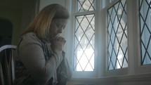 woman praying at a window