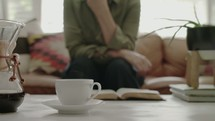 a cup of steaming coffee and a woman sitting on a couch