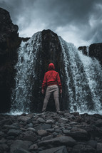 a man standing in front of a waterfall
