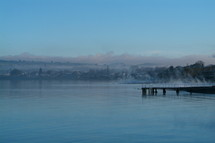 Misty lake view with pier and town in background