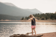 a little girl standing on a lake shore