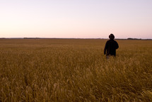 Farmer standing in a wheat field at harvest time