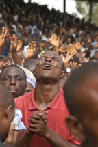 An African man in ernest prayer to God during a worship service in Africa