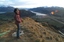 Woman standing on mountain top in the early morning light
