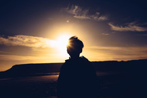 a sunburst behind a silhouette of a boy standing outdoors on a shore