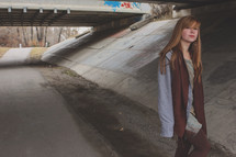 teen girl alone under a bridge