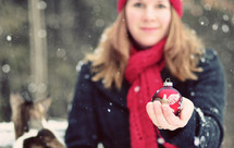 a woman standing in the snow holding a Christmas ornament