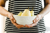 a woman holding a bowl of pears