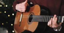 person strumming a guitar