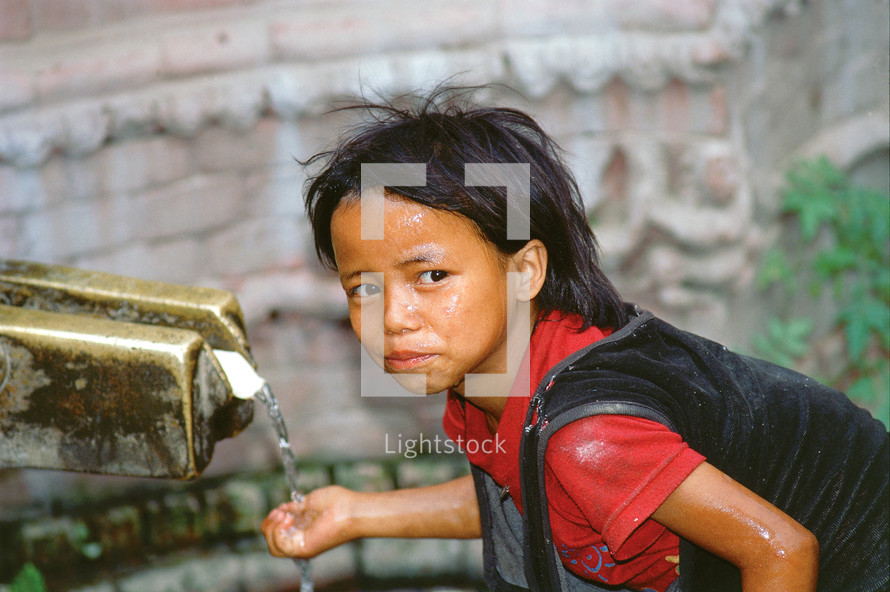 Nepalese girl child washing her hands and drinking from an outdoor spigot [For similar search ethnic smile]