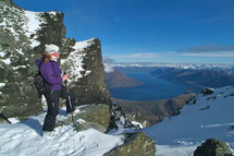 woman standing on top of snow capped mountain ridge overlooking river and mountains