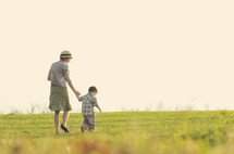 Mother and son walking in a grassy field