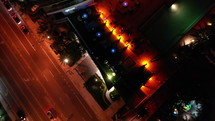 Nighttime aerial top-down bird's eye view of a rooftop bar and streets with passing cars