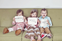 children sitting on a couch holding Easter signs