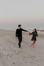 a couple holding hands on a beach