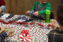 kids unwrapping Christmas gifts at a party