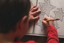 child completing a maze on paper
