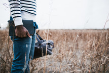 a man standing in a field holding a backpack and a Bible