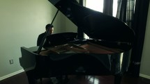 a man playing a grand piano
