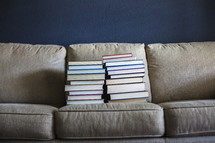 stacked books on a couch