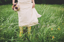 bride walking in a field in rain boots