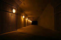 gated tunnel lined with lights leading out of darkness
