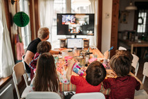children eating candy out of Easter eggs and watching a church service from home