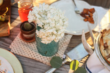 Place settings with  flowers on a picnic table outside.