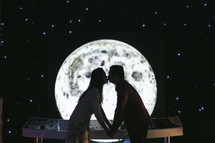 couple kissing in front of the moon