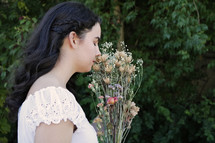 girl in a white dress smelling flowers