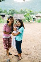 little girls holding a newborn baby in a village