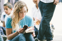 A woman sitting and reading a Bible.