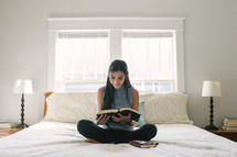 A teen girl sitting on her bed and reading a Bible.