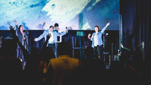 worship leaders performing on stage in front of a projection screen