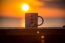 coffee mug with a lighthouse on a banister, and sun a sunrise