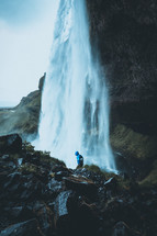 person standing in front of a waterfall