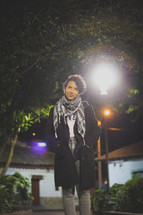 woman standing under a street lamp at night