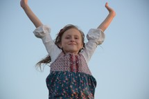 a little girl with raised arms against a blue sky