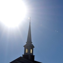 glowing sun over a steeple against a blue sky