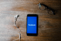 earbuds, Facebook app on a cellphone, and reading glasses on a wood desk